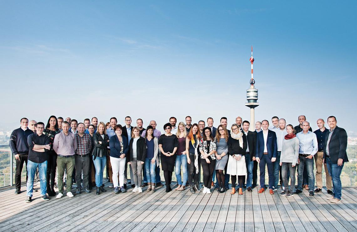 Das Team für die bms-Datenzentrale steht gemeinsam mit den Kolleginnen und Kollegen, die das Projekt international unterstützen, vor dem Donauturm in Wien.